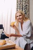 zralá žena v županu, usmívají se na kameru při pití šťávy a pomocí smartphone v hotelovém pokoji