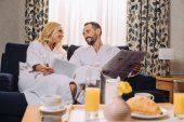 Fotografie smiling mature couple in bathrobes holding newspaper and digital tablet while having breakfast in hotel room