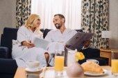 Lächelndes älteres Paar in Bademänteln mit Zeitung und digitalem Tablet beim Frühstück im Hotelzimmer