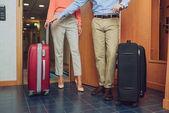 Fotografie oříznutý snímek starší pár s kufry do hotelového pokoje
