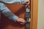 cropped shot of man inserting card into electronic lock in hotel
