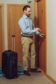 vousatý muž s kufrem drží kartu a otevřete dveře v hotelu
