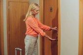 Frau mittleren Alters mit Koffer öffnet elektronisches Schloss in Hotel