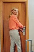 Lächelnde Frau mittleren Alters mit Koffer öffnet elektronisches Schloss im Hotel