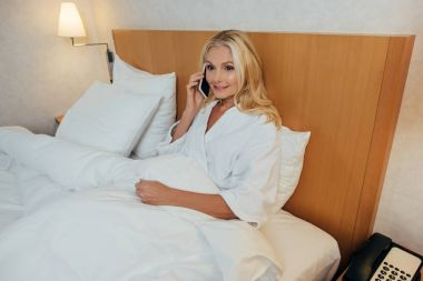 beautiful mature woman in bathrobe talking on smartphone and looking away while lying in bed at hotel room