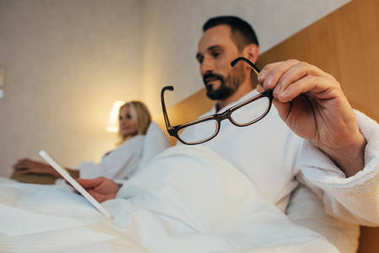 close-up view of bearded mature man holding eyeglasses and using digital tablet in bed