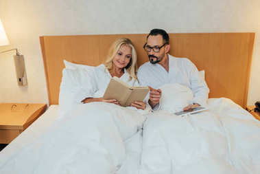 mature couple in bathrobes reading book and using digital tablet in bed in hotel room
