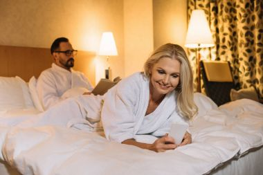 smiling middle aged woman in bathrobe lying on bed and using smartphone while husband reading book behind