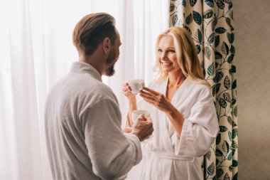 beautiful happy mature couple in bathrobes drinking coffee and smiling each other in hotel room