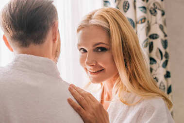 beautiful mature woman smiling at camera while embracing husband in bathrobe in hotel room
