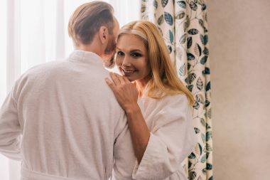 happy mature couple in bathrobes hugging and woman smiling at camera in hotel room