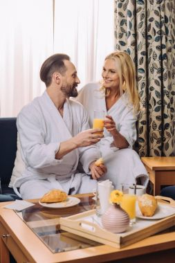 smiling  mature couple in bathrobes having breakfast together in hotel room