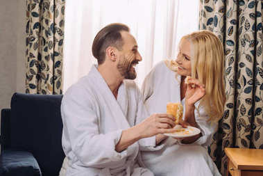 happy mature couple in bathrobes eating pastry for breakfast together in hotel room