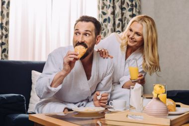 happy mature couple drinking juice and eating pastry during breakfast in hotel room