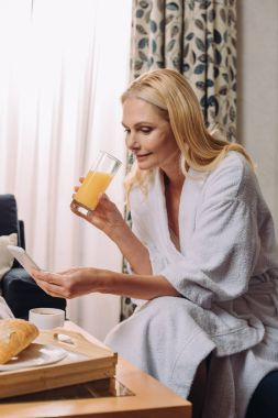 beautiful mature woman in bathrobe drinking juice and using smartphone in hotel room