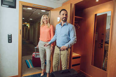 smiling mid adult couple with suitcases looking away while entering in hotel room