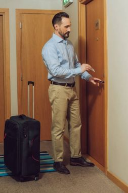 bearded man with suitcase holding card and opening hotel door