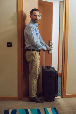 bearded man with suitcase looking at camera while entering hotel room