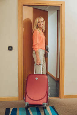 beautiful smiling mature woman with suitcase entering hotel room