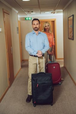 mature couple with suitcases looking at camera while standing in hotel corridor