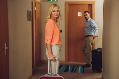 middle aged couple with suitcases looking at camera on hotel corridor