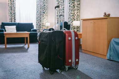 two suitcases standing in empty hotel room