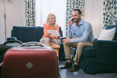 smiling mature couple using smartphone and digital tablet while sitting with suitcases in hotel room