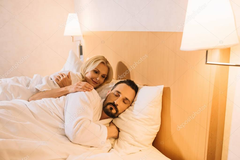 smiling mature woman in bathrobe looking at her husband sleeping in hotel room