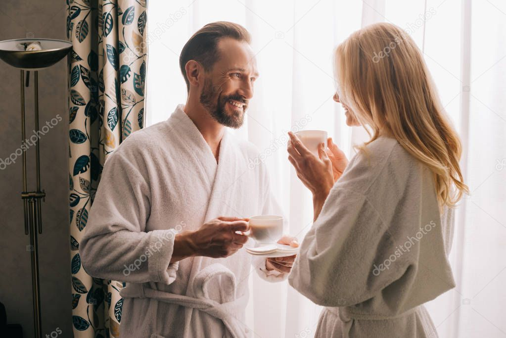 happy middle aged couple in bathrobes drinking coffee and smiling each other in hotel room
