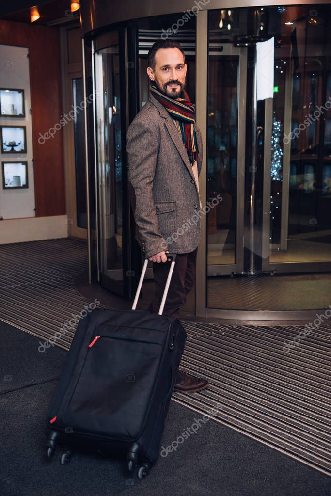 handsome middle aged man with suitcase entering modern hotel