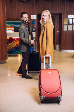 happy mature couple with suitcases standing in hotel hallway
