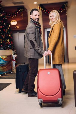 mature couple standing with suitcases and smiling at camera in hotel hallway