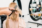 cropped image of hairdresser trimming ends of hair in salon