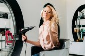 beautiful woman sitting on chair at salon and drying hair