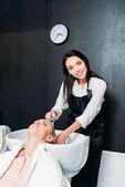 happy hairdresser washing customer hair and looking at camera