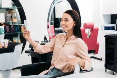 happy woman taking selfie of new hairstyle at salon