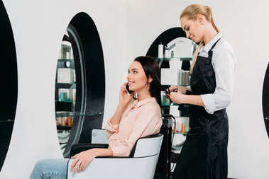 woman talking by smartphone while hairdresser cutting hair