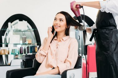 cropped image of customer talking by smartphone while hairdresser drying hair