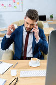aggressive businessman talking by smartphone and crumpling note