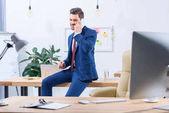 Glücklicher Geschäftsmann, der im Büro per Smartphone spricht