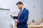 Fotografie serious businessman looking at diagram chart