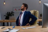 Photo young businessman sitting in chair and having pain in back