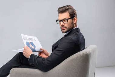 businessman sitting in armchair and holding newspaper