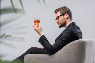 """Картина, постер, плакат, фотообои """"бизнесмен сидит в кресле и смотрит на стакан виски """", артикул 177914236"""