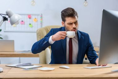 serious businessman drinking coffee and looking at computer