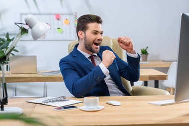happy businessman looking at computer and showing yes gesture