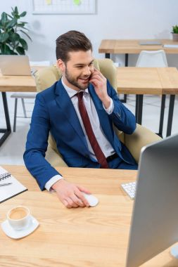 smiling businessman talking by smartphone and looking at computer