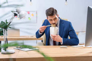 businessman eating noodles and looking at computer