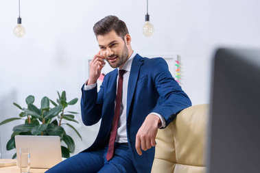 smiling businessman talking by smartphone in office