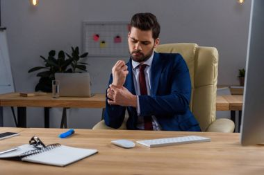 young businessman sitting in chair and having pain in arm